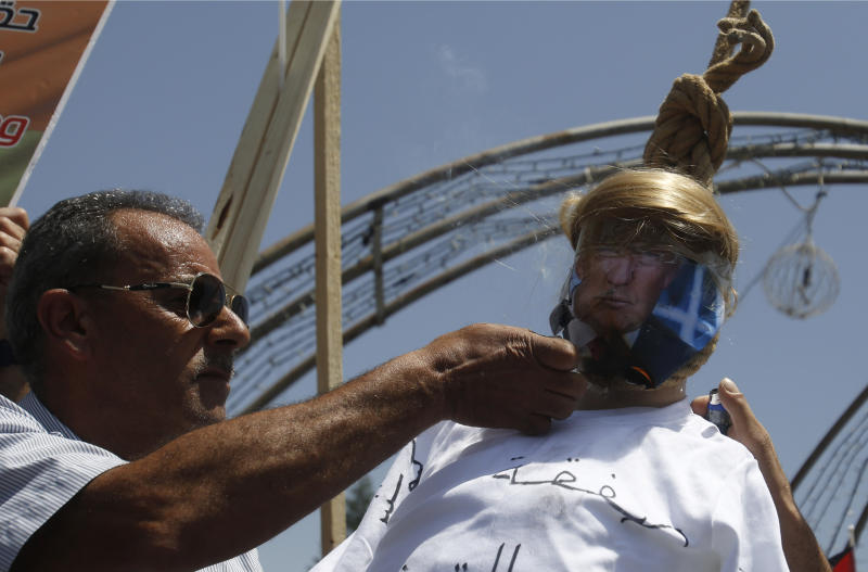 A Palestinian burns an effigy of the US President Donald Trump aduring a protest against the American-led Mideast peace conference in Bahrain, in the West Bank city of Bethlehem, Tuesday, June 25, 2019.(AP Photo/Majdi Mohammed)