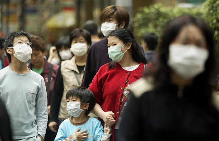 Residents wear masks to protect against a killer outbreak of Severe Acute Respiratory Syndrome (SARS) in the Wanchai district of Hong Kong in 2003. (Peter Parks/AFP via Getty Images)