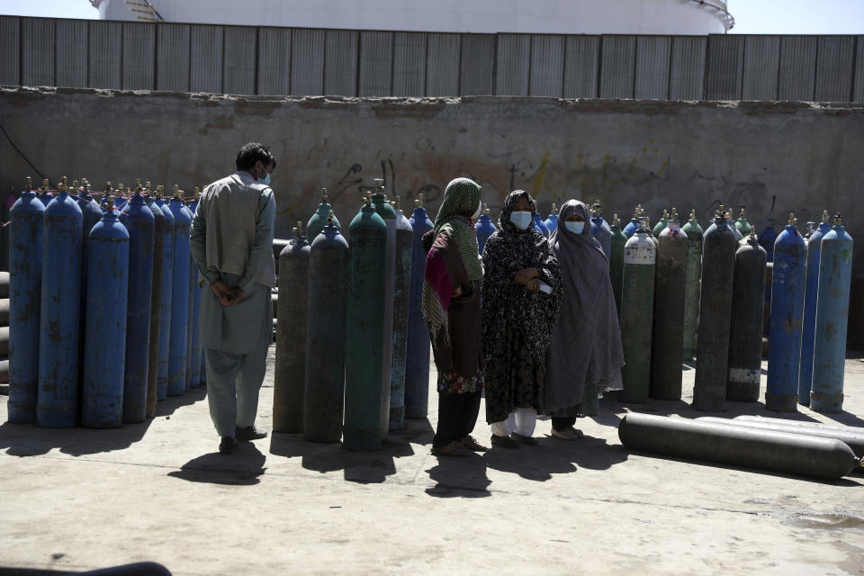 Women wait inside a factory to get their oxygen cylinders refilled from a privately owned oxygen factory, in Kabul, Afghanistan, Saturday, June 19, 2021. Health officials say Afghanistan is fast running out of oxygen as a deadly third surge of COVID worsen. (AP Photo/Rahmat Gul)