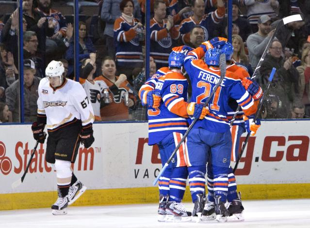 Anaheim Ducks' Rickard Rakell (67) skates past Edmonton Oilers' David Perron (57), Sam Gagner (89) and Andrew Ference (21) as they celebrate a goal during first-period NHL hockey game action in Edmonton, Alberta, Friday, March 28, 2014. (AP Photo/The Canadian Press, Jason Franson)