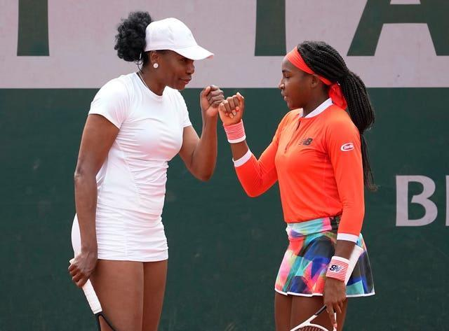 Doubles partners Venus Williams and Coco Gauff bump fists during their first-round loss