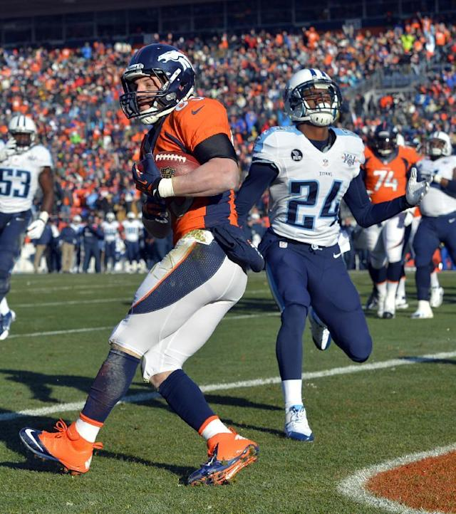 Denver Broncos wide receiver Wes Welker, left, scores past Tennessee Titans cornerback Coty Sensabaugh during the first half of an NFL football game on Sunday, Dec. 8, 2013, in Denver. (AP Photo/Jack Dempsey)