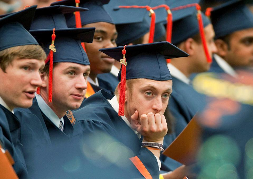 A graduate rests his head in his hand during Syracuse University's commencement ceremony at the Carrier Dome in Syracuse, New York, U.S. (Photo: Michael Okoniewski/Bloomberg via Getty Images)