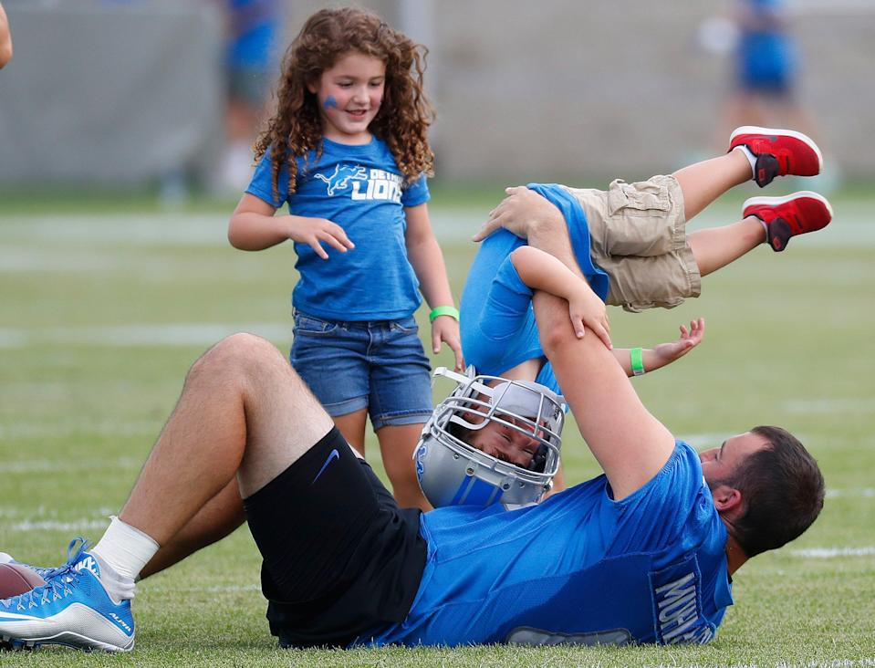 Lions long snapper Don Muhlbach plays with this son Jack as daughter Addison looks on after practice at training camp in Allen Park, July 30, 2017.