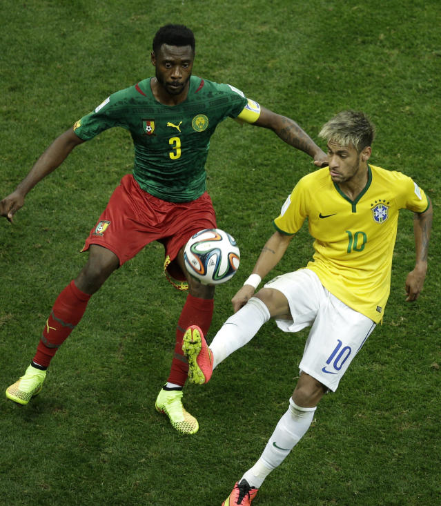 Brazil's Neymar fights for the ball with Cameroon's Nicolas N'Koulou during the group A World Cup soccer match between Cameroon and Brazil at the Estadio Nacional in Brasilia, Brazil, Monday, June 23, 2014. (AP Photo/Christophe Ena)