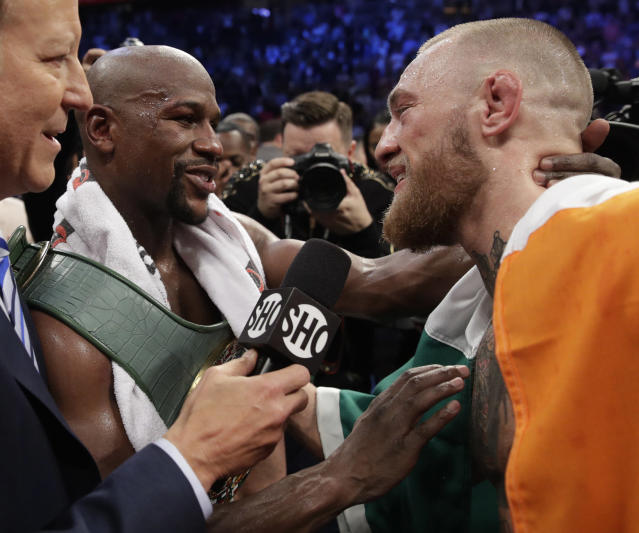 Floyd Mayweather Jr., left, speaks with Conor McGregor after a super welterweight boxing match Saturday, Aug. 26, 2017, in Las Vegas. (AP)