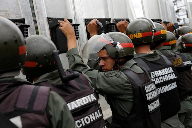 <p>Venezuelan National Guards take cover behind their shields as they recover from tear gas, in Caracas, Venezuela, June 7, 2016. (Reuters/Carlos Garcia Rawlins) </p>