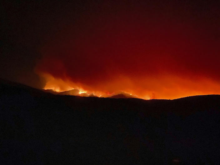 This Monday, June 7, 2021, photo provided by Arizona Rep. David Cook, a rancher who lives out of Globe, Ariz., shows flames and smoke rising from a ridge near his home. Firefighters in Arizona were fighting Tuesday to gain a foothold into a massive wildfire, one of two that has forced thousands of evacuations in rural towns and closed almost every major highway out of the area. (David Cook via AP)