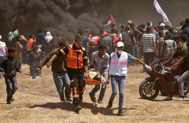 <p>Palestinians carry a demonstrator injured during clashes with Israeli forces near the border between the Gaza Strip and Israel east of Gaza City on May 14, 2018, as Palestinians protested the inauguration of the U.S. Embassy following its controversial move to Jerusalem. (Photo: Mahmud Hams/AFP/Getty Images) </p>