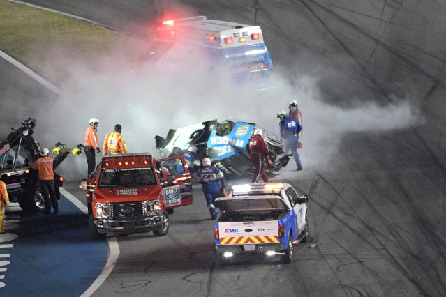 Track personnel arrive to help Ryan Newman (6) after he flipped his car on the final lap in front of the grandstands during the NASCAR Daytona 500 auto race at Daytona International Speedway, Monday, Feb. 17, 2020, in Daytona Beach, Fla. (AP Photo/Phelan M. Ebenhack)