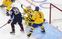 Sweden goalie Hugo Alnefelt (30) looks back at the puck on a goal as United States' Arthur Kaliyev (28) and Tobias Bjornfot (3) wait for a possible rebound during the second period of an IIHF World Junior Hockey Championship game Thursday, Dec. 31, 2020, in Edmonton, Alberta. (Jason Franson/The Canadian Press via AP)
