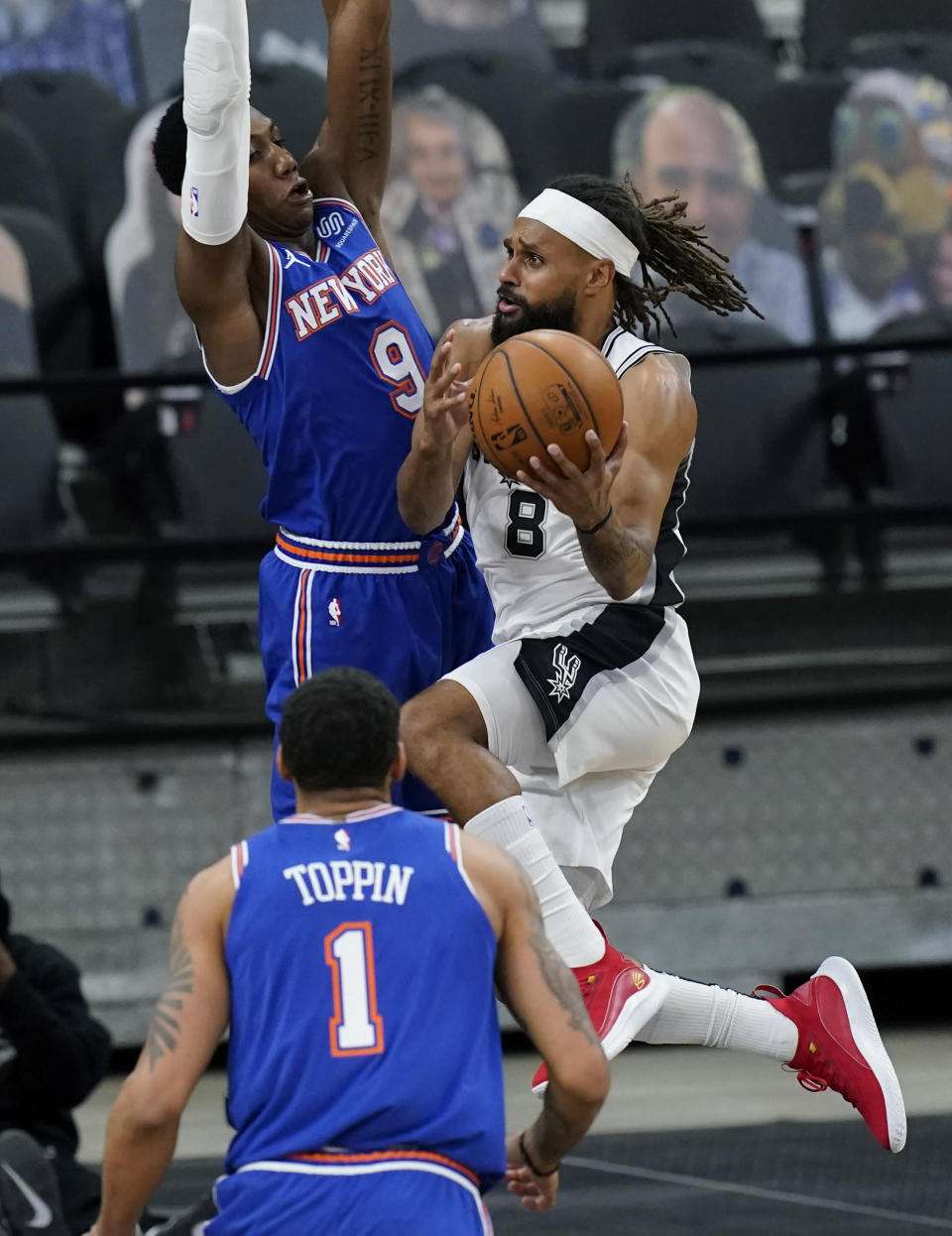 San Antonio Spurs guard Patty Mills (8) drives to the basket against New York Knicks guard RJ Barrett (9) during the second half of an NBA basketball game in San Antonio, Tuesday, March 2, 2021. (AP Photo/Eric Gay)