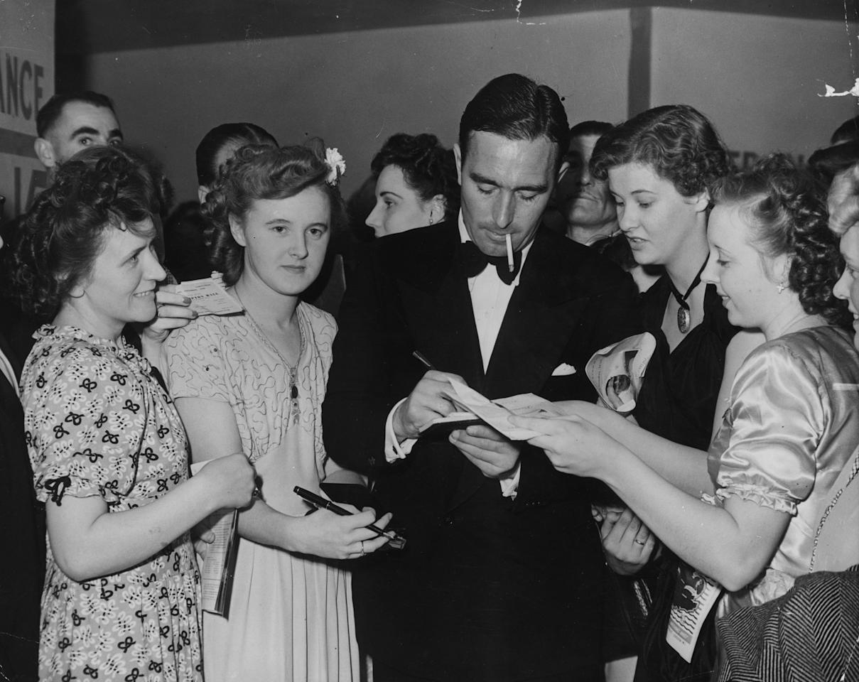 Young fans seek the autograph of England cricketer and journalist, Denis Compton during the Denis Compton Ball, held at the Empress Hall.   (Photo by Keystone/Getty Images)