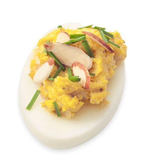 """<p>Add color and flavor to your deviled egg with a little curry. Transfer the yolks from 6 hard-cooked eggs into a bowl and add in 1/4 cup mayo. Mix with 1 teaspoon each curry powder and lemon juice, and 1/8 teaspoon salt. Spoon into whites; top with sliced almonds and snipped chives.</p><p><em><strong>Recipe courtesy of <a href=""""https://www.goodhousekeeping.com/food-recipes/easy/g606/deviled-eggs-recipes"""" rel=""""nofollow noopener"""" target=""""_blank"""" data-ylk=""""slk:Good Housekeeping"""" class=""""link rapid-noclick-resp"""">Good Housekeeping</a>. </strong></em></p>"""