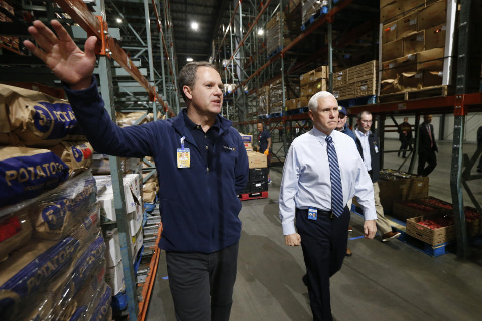 Vice President Mike Pence, right, walks with Walmart president and CEO Doug McMillon, as they tour a Walmart Distribution Center Wednesday, April 1, 2020, in Gordonsville, Va. (AP Photo/Steve Helber)