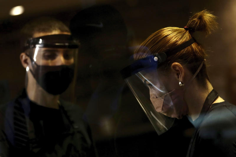 Hairdressers wear face shields and masks for protection amid the COVID-19 pandemic while attending clients on the first day the saloon was allowed to reopen, as restrictions ease in Brasilia, Brazil, Wednesday, July 15, 2020. (AP Photo/Eraldo Peres)