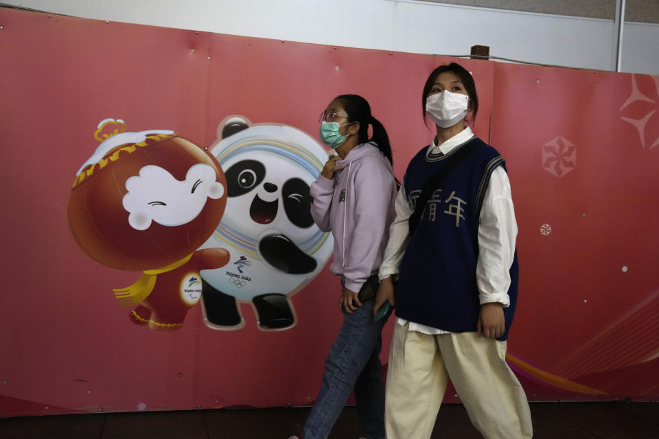 Residents wearing masks pass by the mascots for the Beijing Winter Olympics and Paralympics in Beijing Sunday, Oct. 3, 2021. When the International Olympic Committee awarded Beijing the 2008 Summer Olympics, it promised the Games could improve human rights and civil liberties in China. (AP Photo/Ng Han Guan)