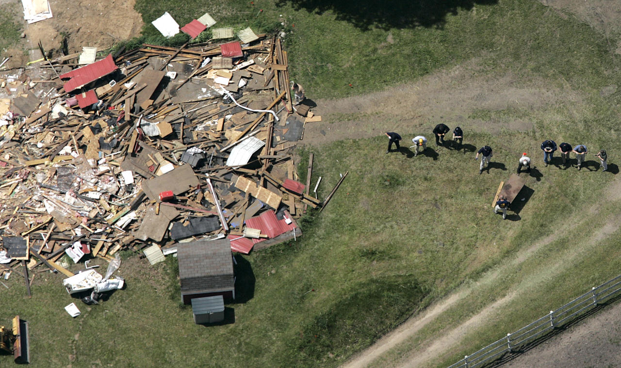 FILE - In this May 24, 2006, file photo, workers, including Federal Bureau of Investigation evidence response team members, probe the ground near a demolished barn at a horse farm in Milford Township, Mich., where FBI agents investigating Jimmy Hoffa's 1975 disappearance were working for an eighth day. Hoffa's mysterious disappearance, assumed death and myriad searches for his body have been the stuff of urban legends for more than three decades. (AP Photo/Paul Sancya, File)