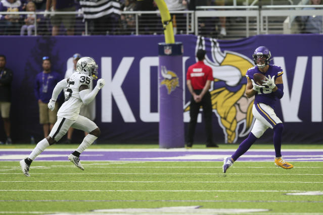 Minnesota Vikings wide receiver Adam Thielen catches a 35-yard touchdown pass ahead of Oakland Raiders free safety Curtis Riley, left, during the first half of an NFL football game, Sunday, Sept. 22, 2019, in Minneapolis. (AP Photo/Jim Mone)