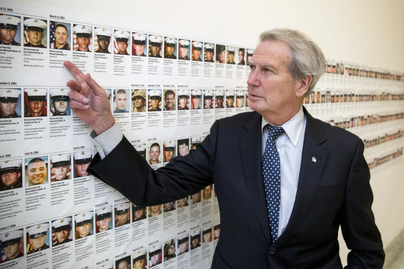 FILE - In this Oct. 25, 2017, file photo, U.S. Rep. Walter Jones, R-N.C., points at a photograph of Marine Sgt. Michael Edward Bits of Ventura, Calif., the first military funeral he and his wife attended, and one of the many pictures of soldiers killed this century based at Camp Lejeune, N.C., along a hallway leading to his office on Capitol Hill in Washington. Jones, a once-fervent supporter of the 2003 invasion of Iraq who later became an equally outspoken Republican critic of the war, died Sunday, Feb. 10, 2019, his 76th birthday. (AP Photo/Andrew Harnik, File)