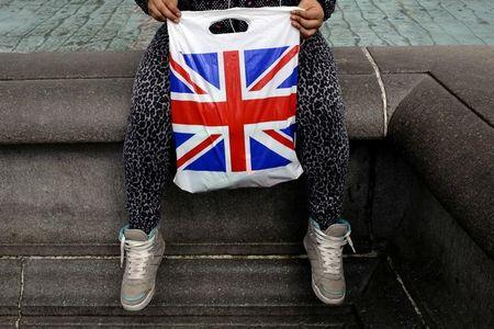 FILE PHOTO - A woman holds a Union Flag shopping bag in London, Britain April 23, 2016.  REUTERS/Kevin Coombs/File Photo