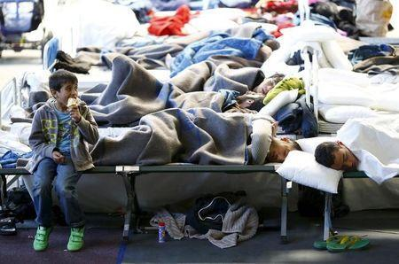 Migrants rest at a temporary shelter in a sports hall in Hanau, Germany, October 1, 2015. REUTERS/Kai Pfaffenbach