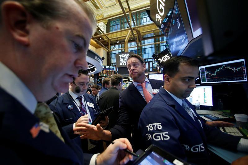 Traders work on the floor of the NYSE as the Dow Jones Industrial Average passes the 20,000 mark in New York
