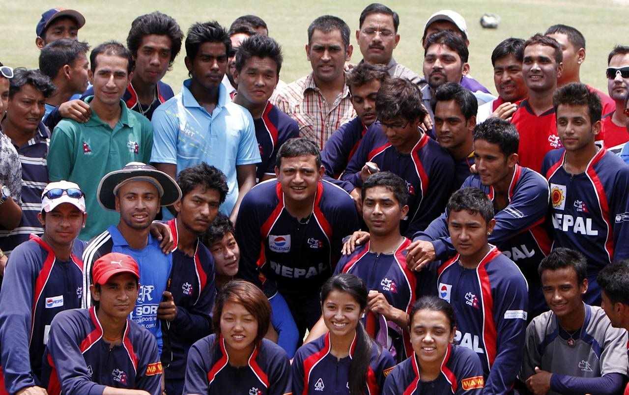 Indian cricket team captain Mahendra Singh Dhoni (C back) interacts with the Nepali cricket team at Tribhuvan University Cricket ground in Kathmandu on 16, June 2012. Dhoni arrived in Nepal for a one day visit. AFP PHOTO/ STR        (Photo credit should read STR/AFP/GettyImages)
