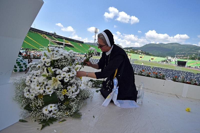 A nun arranges flowers on the stage at Sarajevo city stadium on June 5, 2015, a day ahead of a visit by Pope Francis (AFP Photo/Andrej Isakovic)