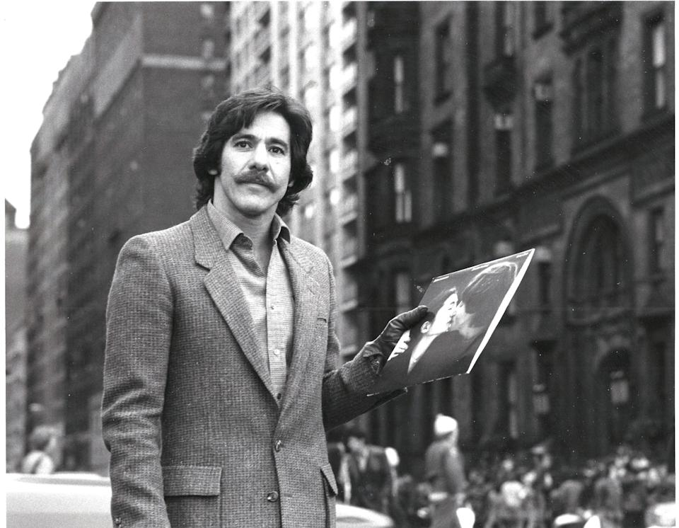 Geraldo Rivera holding a John Lennon album outside of the Dakota, the building where Lennon lived — and was murdered in front of in 1980. (Photo: Fox Nation)