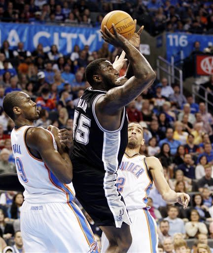 San Antonio Spurs center DeJuan Blair, center, shoots between Oklahoma City Thunder forward Serge Ibaka, (9) of Republic of Congo, and guard Thabo Sefolosha (2), of Switzerland, in the first quarter of an NBA basketball game in Oklahoma City, Friday, March 16, 2012. (AP Photo/Sue Ogrocki)
