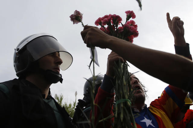 <p>People try to offer flowers to a civil guard at the entrance of a sports center, assigned to be a referendum polling station by the Catalan government in Sant Julia de Ramis, near Girona, Spain, Oct. 1, 2017. Scuffles have erupted as voters protested while dozens of anti-rioting police broke into a polling station where the regional leader was expected to show up for voting on Sunday. (Photo: Francisco Seco/AP) </p>