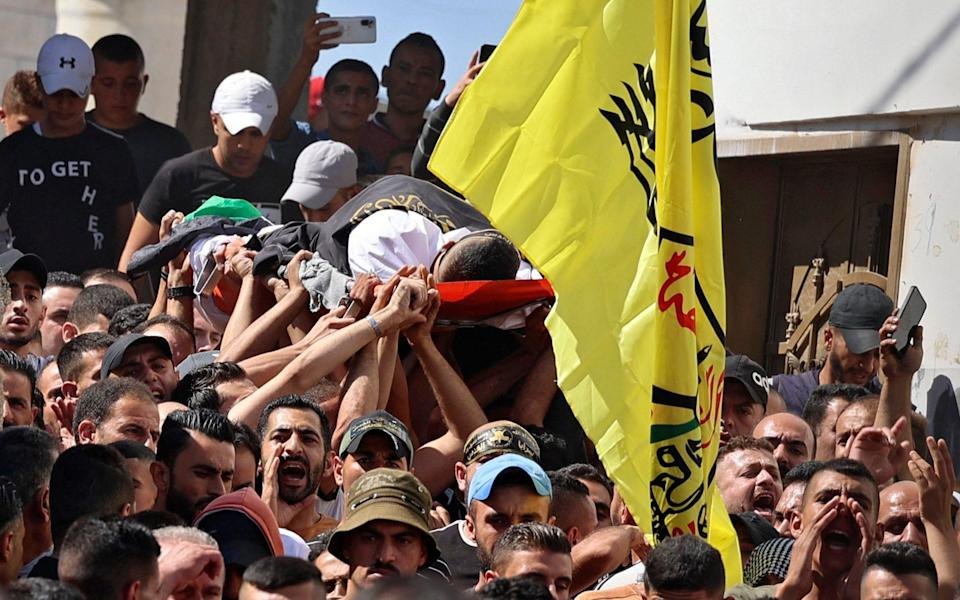 Mourners carry the body of Osama Sobh, a Palestinian killed by Israeli soldiers during clashes near Jenin - JAAFAR ASHTIYEH /AFP