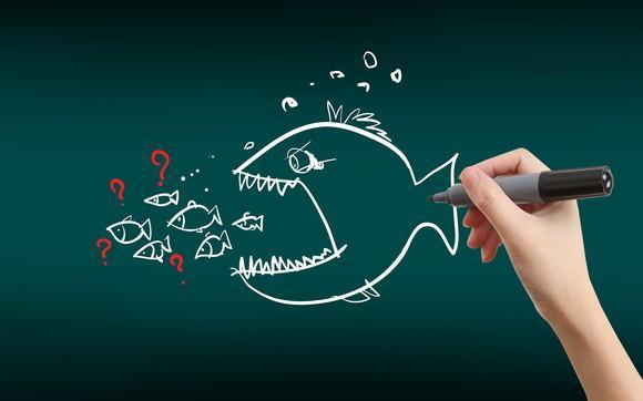 Hand holding marker with drawing of big fish with mouth open next to several small fish with question marks around them