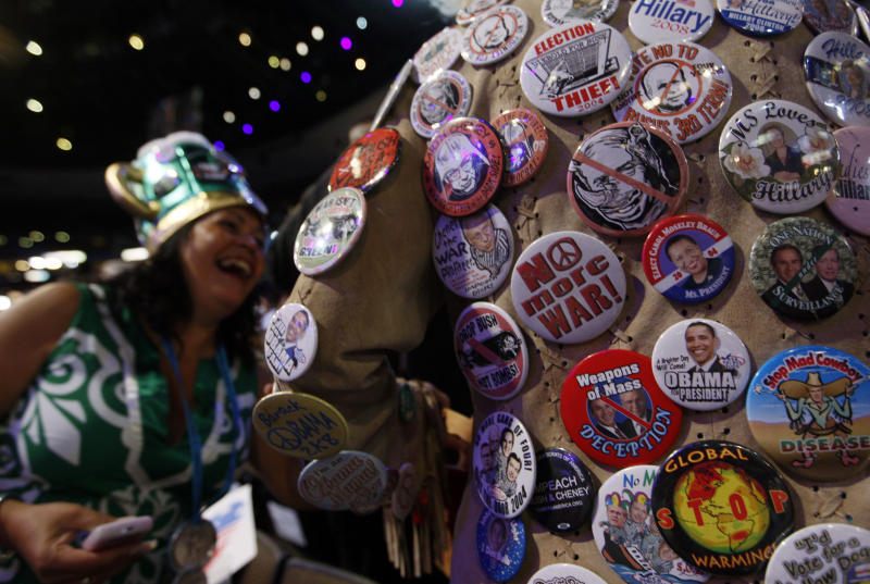 FILE - In this Aug. 26, 2008, file photo, delegate Kelly Jacobs, of Hernando, Miss., shows off her many buttons to Awilda Cordero, a delegate from Bronx, N.Y., left, during the Democratic National Convention in Denver. Viewer interest in the 2012 Republican and Democratic national conventions is still unclear. With the parties' quadrennial presidential nominating gatherings fast approaching, organizers on both sides are bedeviled by a similar challenge: how to ensure TV viewer interest in the multiday affairs, which threaten to be largely predictable spectacles nearly devoid of suspense (AP Photo/Charles Dharapak, File)