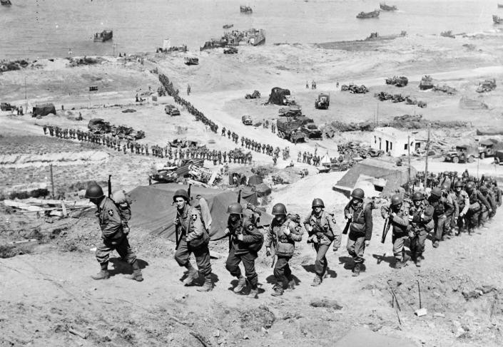U.S. Army reinforcements march up a hill past a German bunker overlooking Omaha Beach after the D-Day landings near Colleville-sur-Mer, France, on June 18, 1944. (Photo: U.S. National Archives/handout via Reuters)