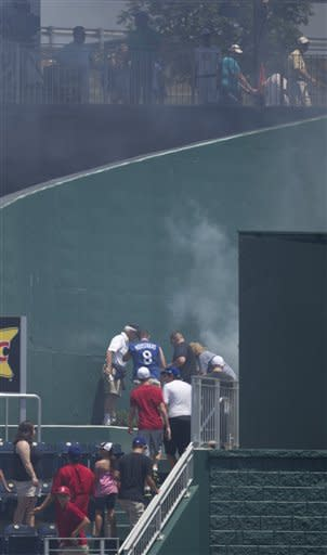 Smoke rises from a fire caused by pre-game fireworks behind the outfield wall of Kauffman Stadium during the first inning of a baseball game between the Chicago White Sox and Kansas City Royals in Kansas City, Mo., Sunday, July 15, 2012. (AP Photo/Orlin Wagner)