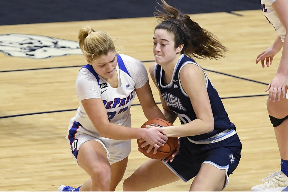 DePaul's Dee Bekelja, left, and Villanova's Maddy Siegrist, right, fight for possession of the ball during overtime of an NCAA college basketball game in the quarterfinals of the Big East Conference tournament at Mohegan Sun Arena, Saturday, March 6, 2021, in Uncasville, Conn. (AP Photo/Jessica Hill)