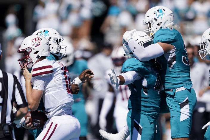 Coastal Carolina linebacker Myles Olufemi, middle, celebrates after sacking Massachusetts quarterback Brady Olson with linebacker Teddy Gallagher during the first half of an NCAA college football game on Saturday, Sept. 25, 2021, in Conway, S.C. (AP Photo/Chris Carlson)