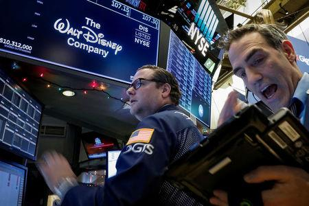Traders work at the post where Walt Disney Co. stock is traded on the floor of the New York Stock Exchange (NYSE) in New York, U.S., December 14, 2017. REUTERS/Brendan McDermid