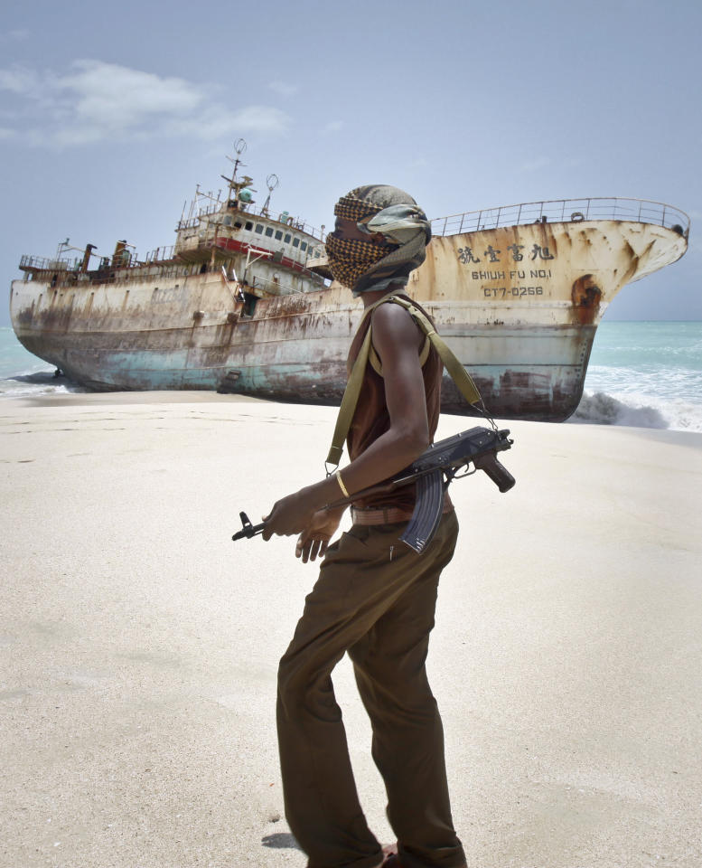 In this photo taken Sunday, Sept. 23, 2012, masked Somali pirate Abdi Ali walks past a Taiwanese fishing vessel that washed up on shore after the pirates were paid a ransom and released the crew, in the once-bustling pirate den of Hobyo, Somalia. The empty whisky bottles and overturned, sand-filled skiffs that litter this shoreline are signs that the heyday of Somali piracy may be over - most of the prostitutes are gone, the luxury cars repossessed, and pirates talk more about catching lobsters than seizing cargo ships. (AP Photo/Farah Abdi Warsameh)