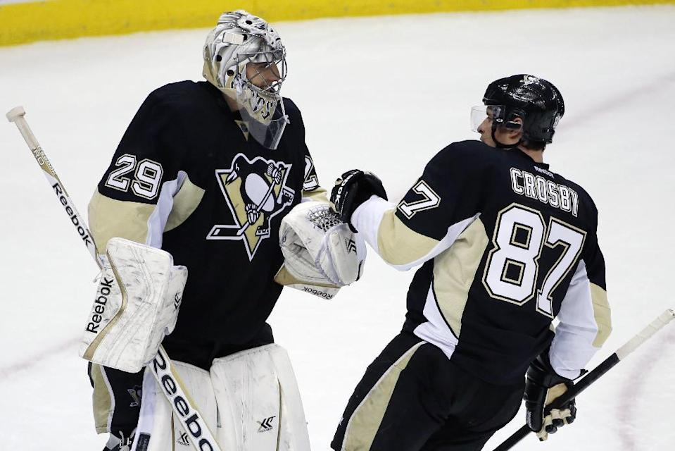 Pittsburgh Penguins goalie Marc-Andre Fleury (29) celebrates with Sidney Crosby (87) after a 4-3 win over the Columbus Blue Jackets in a first-round NHL playoff hockey game in Pittsburgh on Wednesday, April 16, 2014.(AP Photo/Gene J. Puskar)