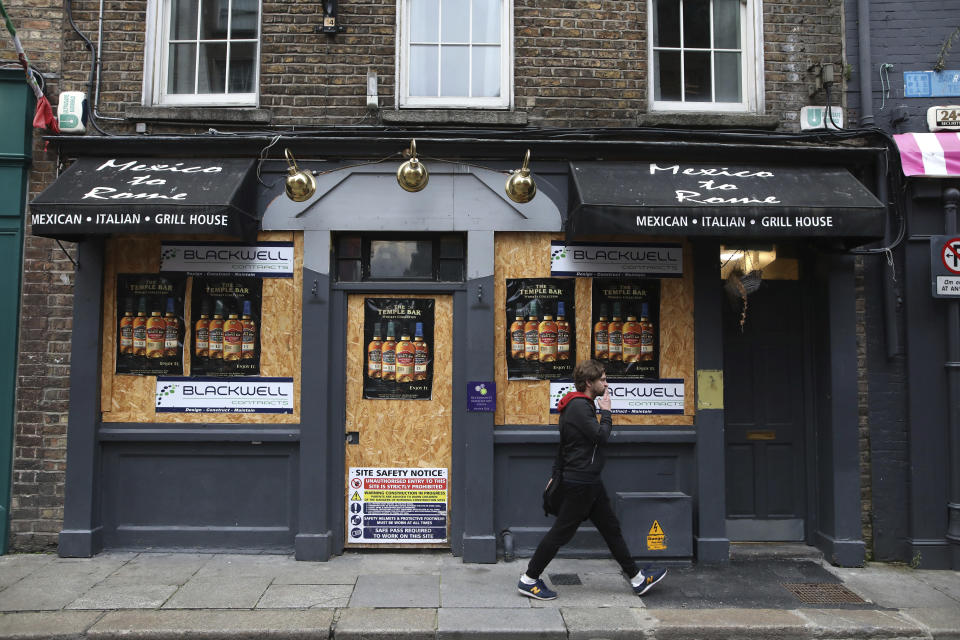 A man walks past a boarded up restaurant in Dublin, Ireland, Wednesday, Oct. 21, 2020. With COVID-19 cases on the rise, the government has imposed a tough new lockdown, shutting down non-essential shops, limiting restaurants to takeout service and ordering people to stay within five kilometers (three miles) of their homes for the next six weeks. (AP Photo/Peter Morrison)