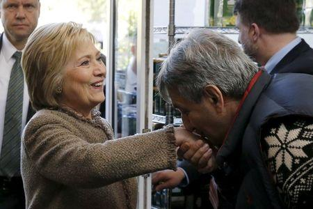 Saffron Cafe and Bakery owner Ali Rahnamoon kisses the hand of U.S. Democratic Presidential candidate Hillary Clinton as she arrives to greet voters at his cafe in Charleston