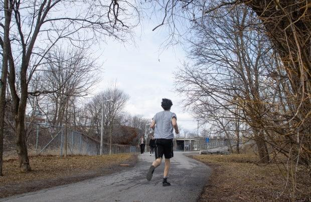 A runner heads north on the path along Ottawa's Trillium O-Train line on March 25, 2021, during warm spring weather. Exercising alone outside is considered safe by Ottawa Public Health as long as people distance from others. (Trevor Pritchard/CBC - image credit)