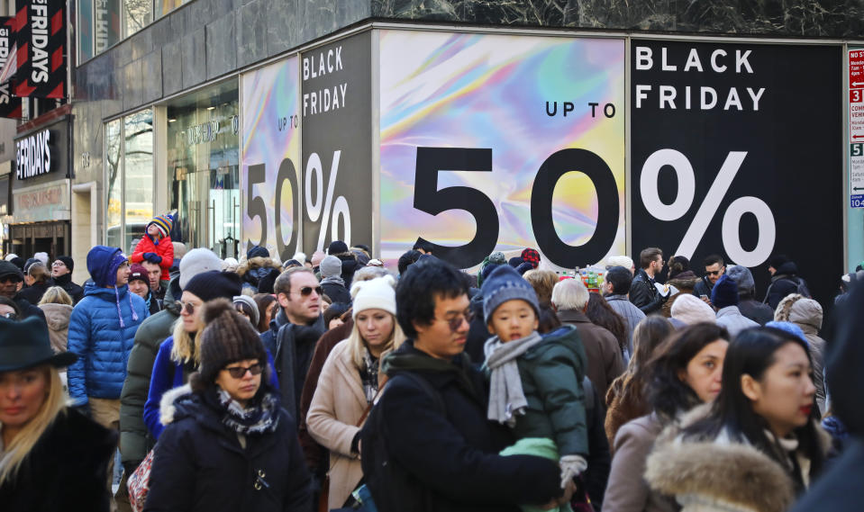 Crowds walk past a large store sign displaying a Black Friday discount in midtown Manhattan, Friday, Nov. 23, 2018, in New York. The holiday shopping season presents a big test for a U.S. economy, with overall growth so far this year relying on a burst of consumer spending. (AP Photo/Bebeto Matthews)