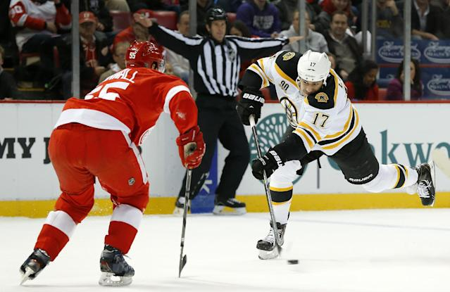 Boston Bruins left wing Milan Lucic (17) shoots against Detroit Red Wings defenseman Niklas Kronwall (55), of Sweden, in the first period of an NHL hockey game in Detroit, Wednesday, Nov. 27, 2013. (AP Photo/Paul Sancya)