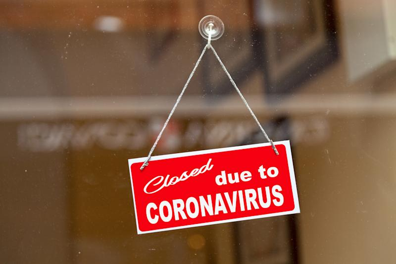 "Red sign hanging at the glass door of a shop saying ""Closed due to coronavirus""."