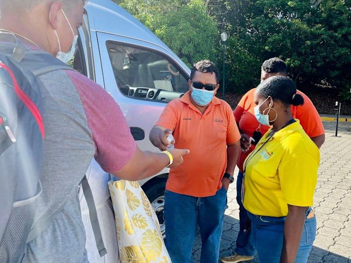 A driver passing out hand sanitizer before boarding a van.