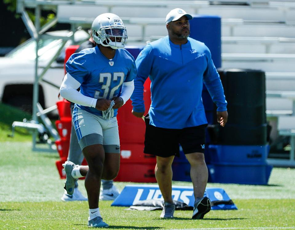 Detroit Lions running back D'Andre Swift (32) and assistant coach Duce Staley during organized team activities at Lions headquarters in Allen Park, Thursday, May 27, 2021.